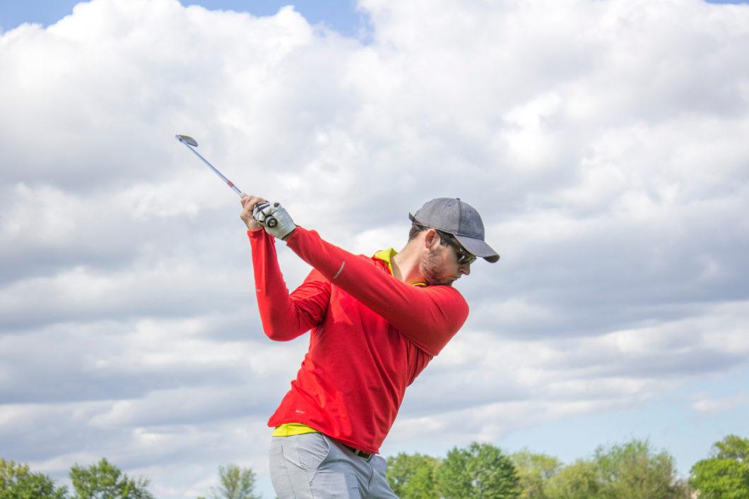Man in red shirt golfing