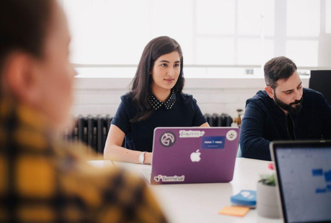 Woman at a purple laptop amongst study group