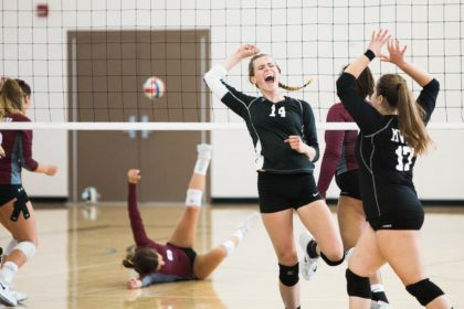 Female Volleyball team celebrates while opponent falls to the ground and might have a concussion