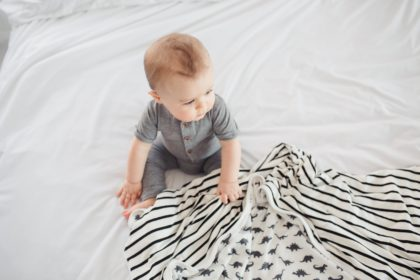 Baby in grey clothes sitting on white linen clutching dinosaur blanket